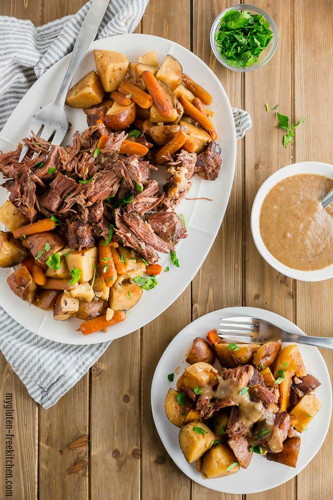 Gluten-free Slow Cooker Pot Roast on a platter with a bowl of gravy beside it