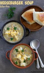 2 bowls of gluten-free cheeseburger soup with spoons and rolls