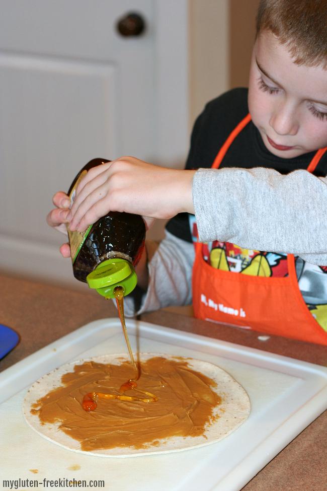 Making peanut butter and honey tortilla roll ups