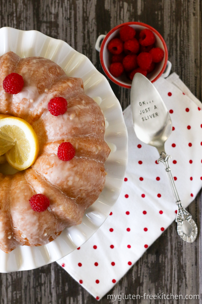 gluten-free lemon cake on platter with cake server beside it and raspberries