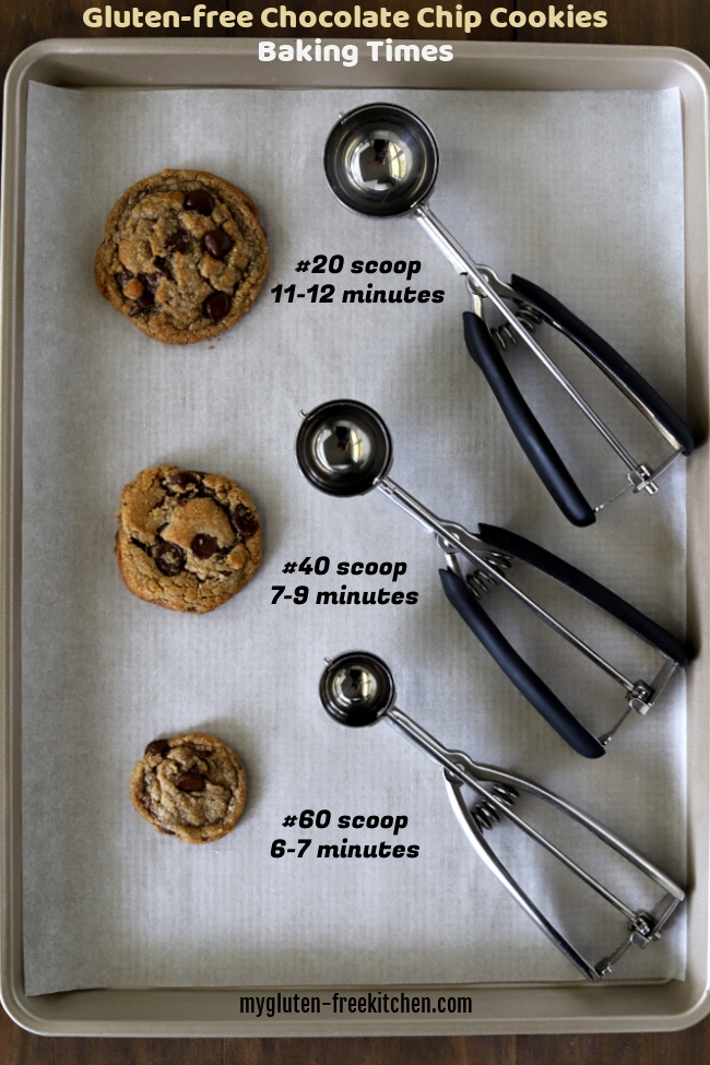 Three different sizes of gluten-free chocolate chip cookies on cookie sheet with three cookie scoops beside them