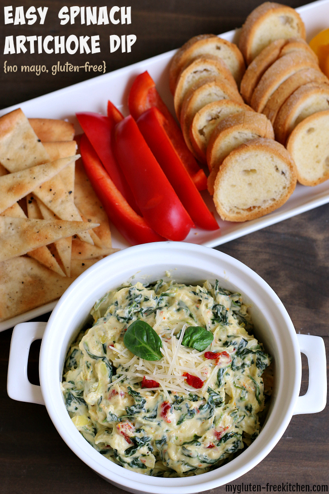 bowl of spinach artichoke dip alongside sliced bell peppers.