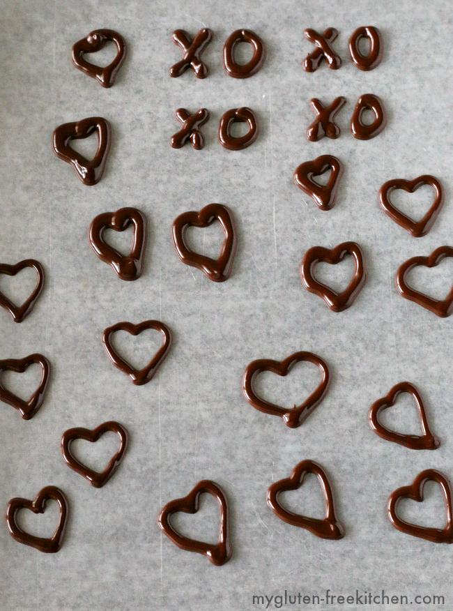 Practicing making Chocolate Heart Decorations. Using melted chocolate with a bit of shortening to make chocolate decorations.