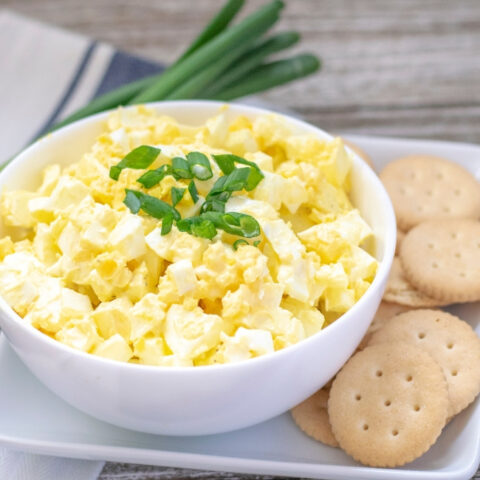 Bowl of egg salad with crackers next to it