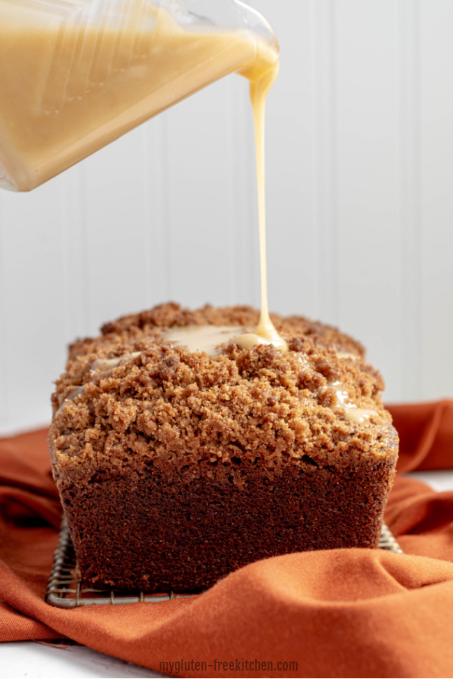 pouring maple glaze on loaf of Gluten-free Pumpkin Bread